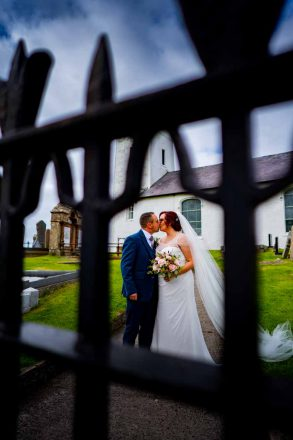 newly weds kissing outside a church